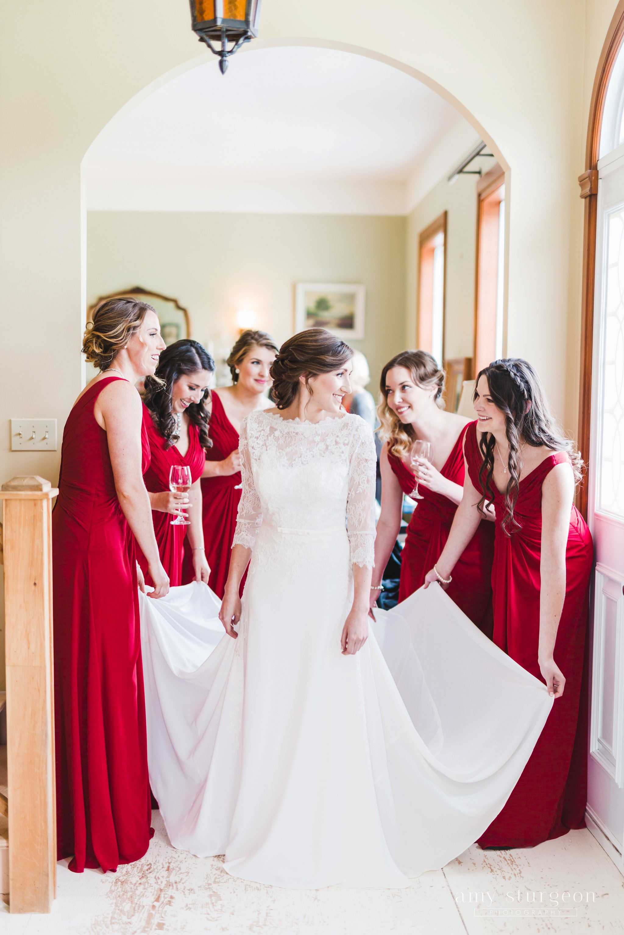 The bridesmaids helped the bride get in to her dress at the alpaca farm wedding in ottawa