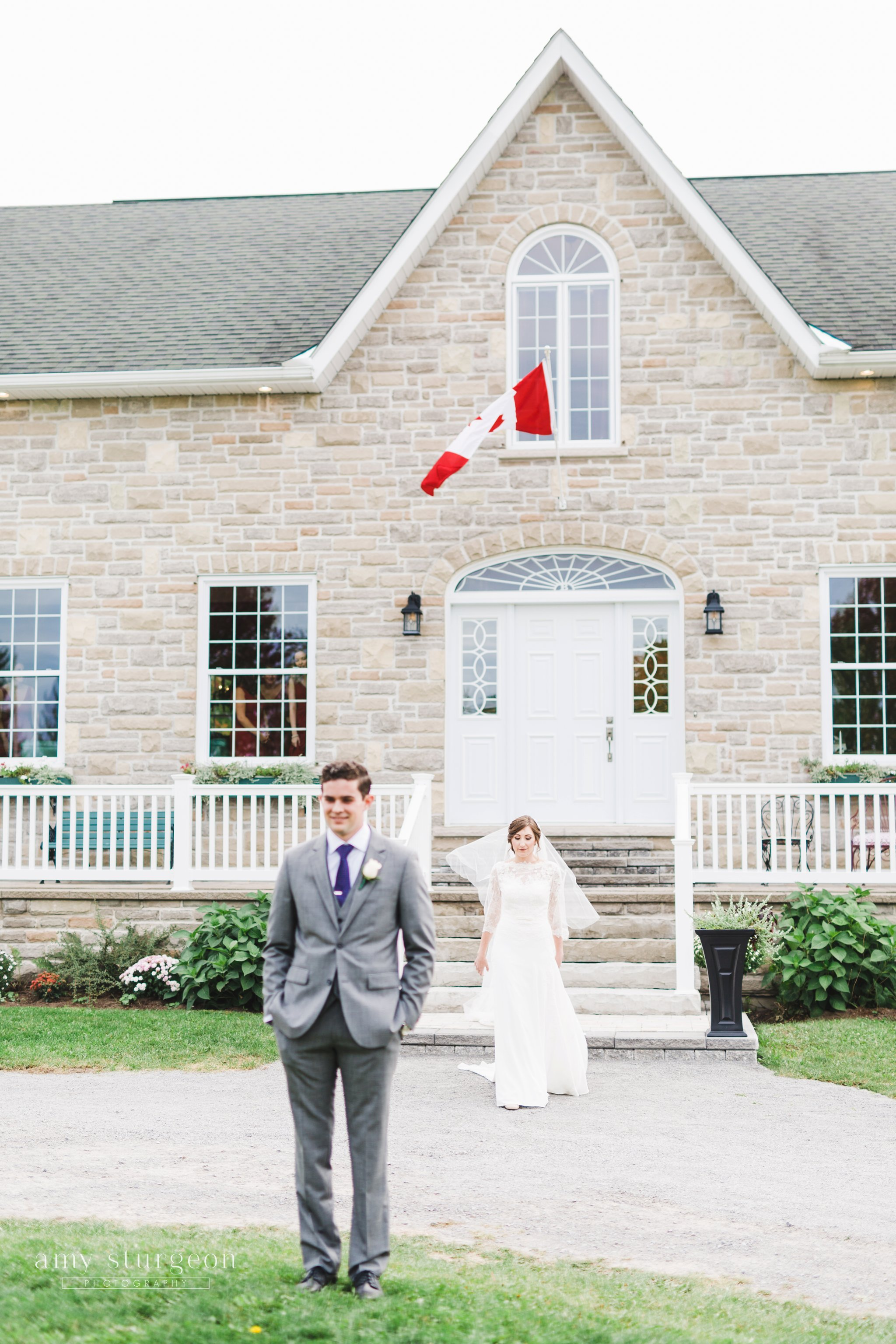 The bride walked from the house towards her future husband for their first look at the alpaca farm wedding in ottawa