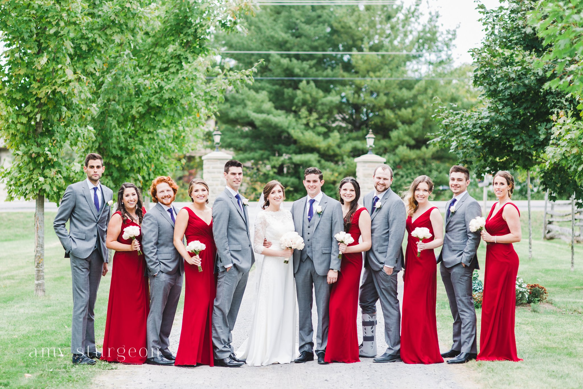 Red bridesmaids dress with grey suits looks great together at the alpaca farm wedding