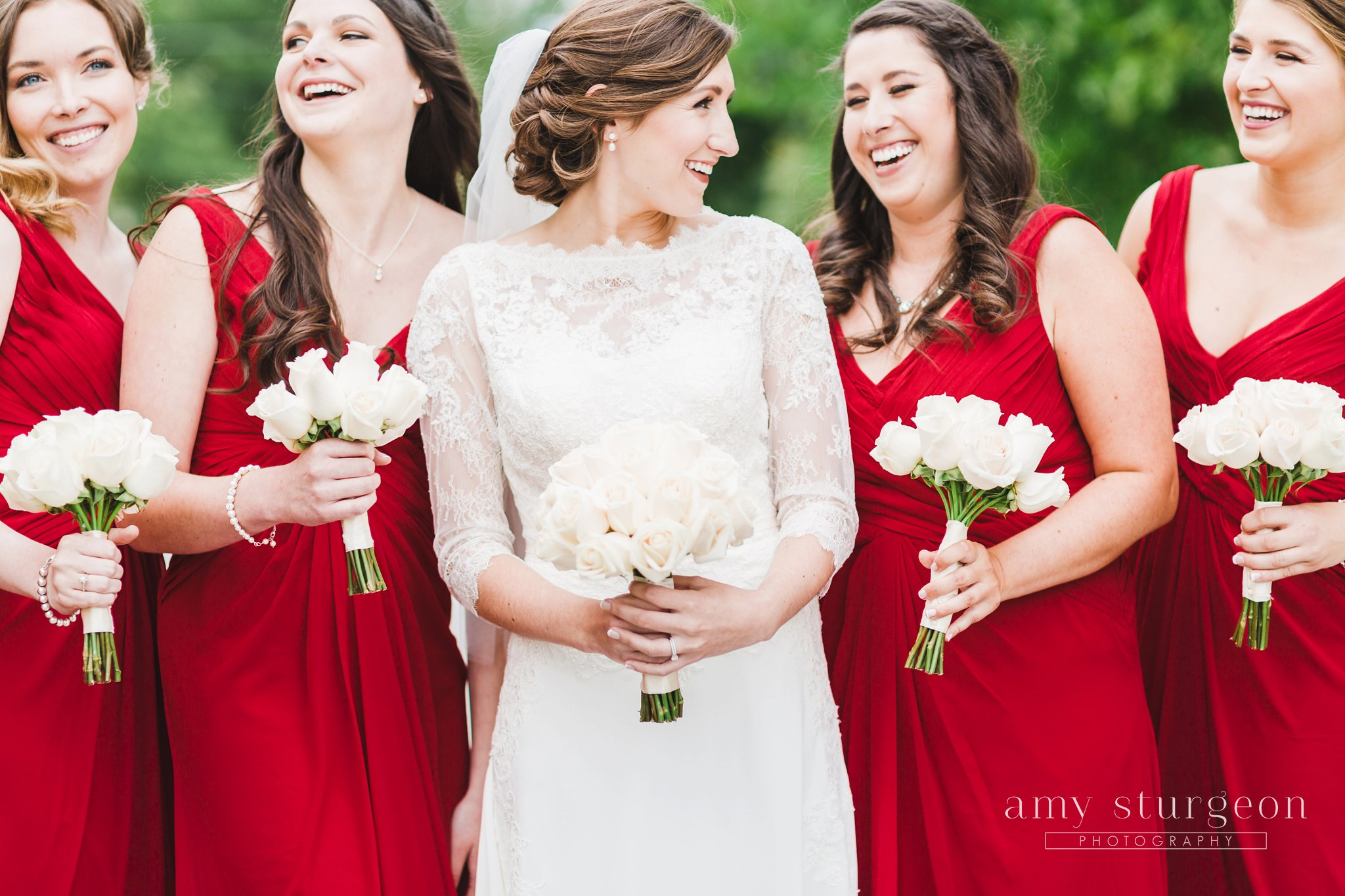 red bridesmaids dresses with white rose bouquets at the alpaca farm wedding