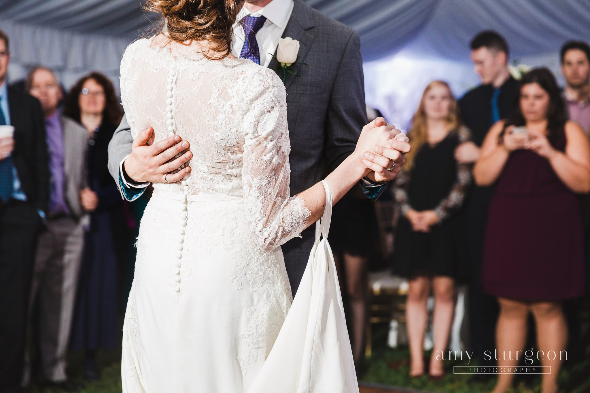 The bride's dress had the most intricate lace sleeves with white satin buttons at the alpaca farm wedding