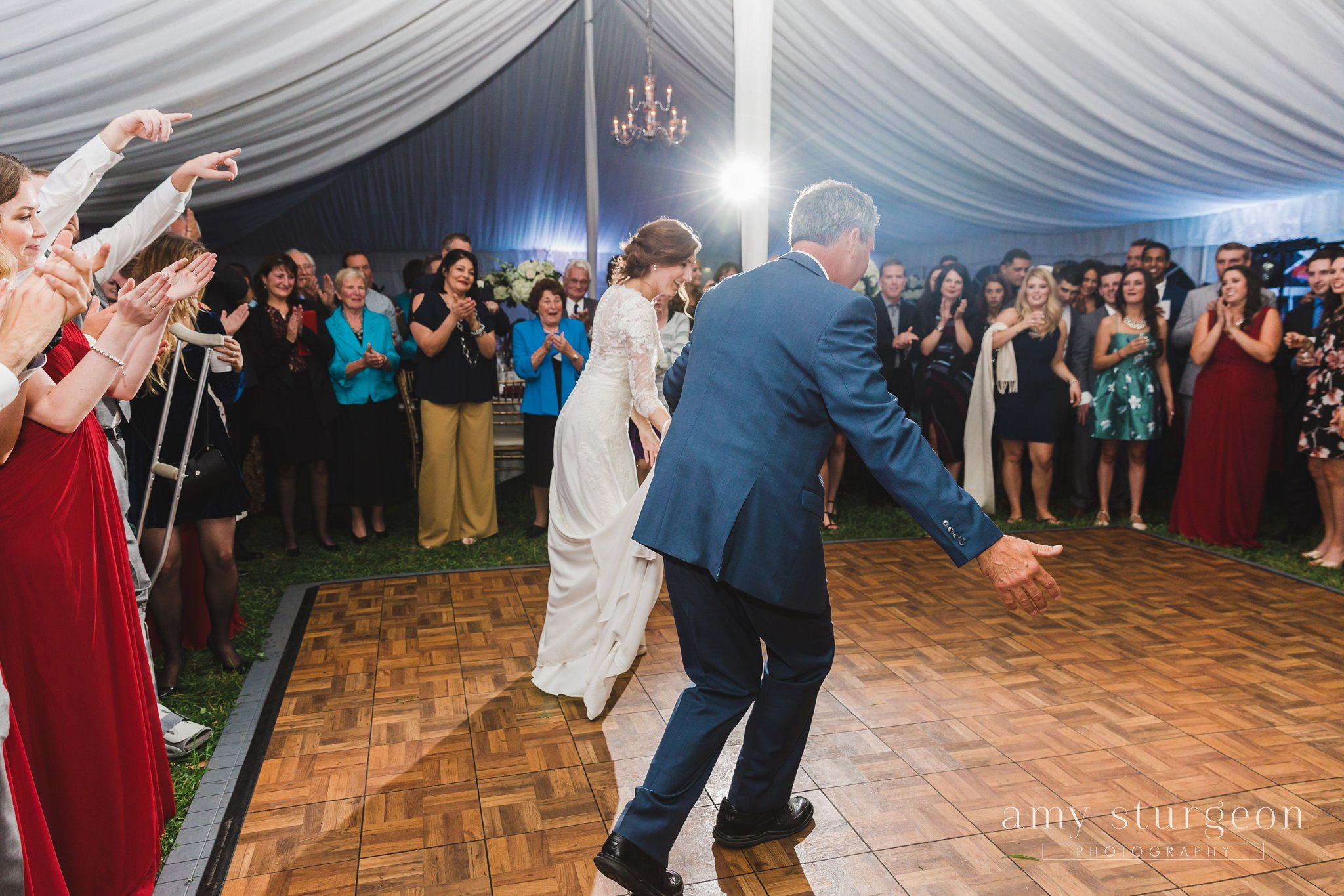The guests cheered as the bride and her father took a bow after their father-daughter dance at the alpaca farm wedding