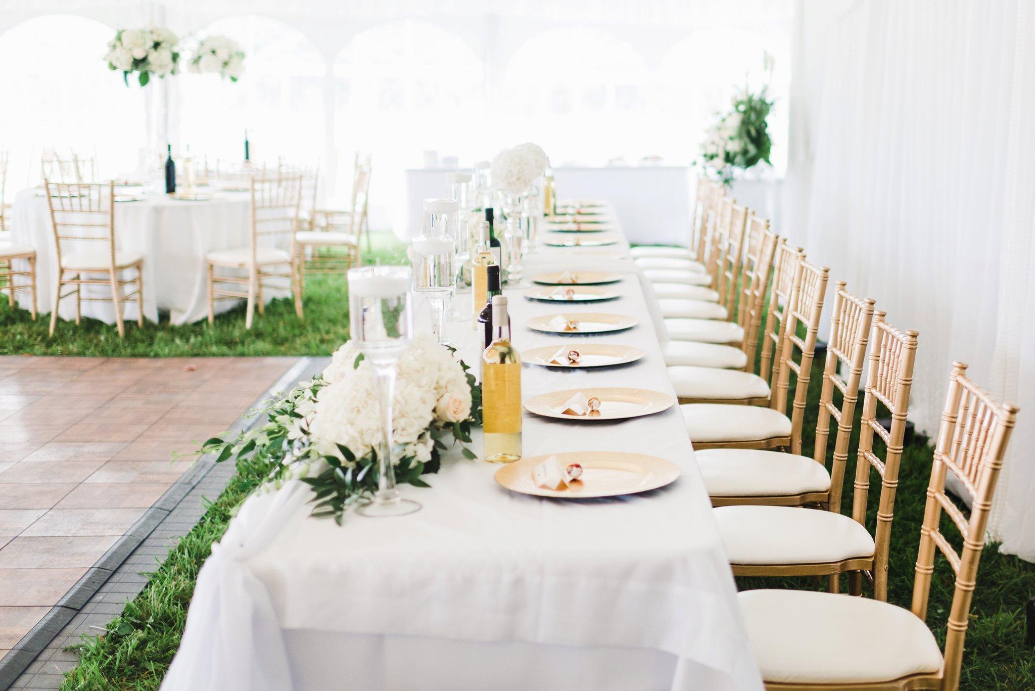 Gold chiavari chairs under the white wedding tent at the alpaca farm wedding