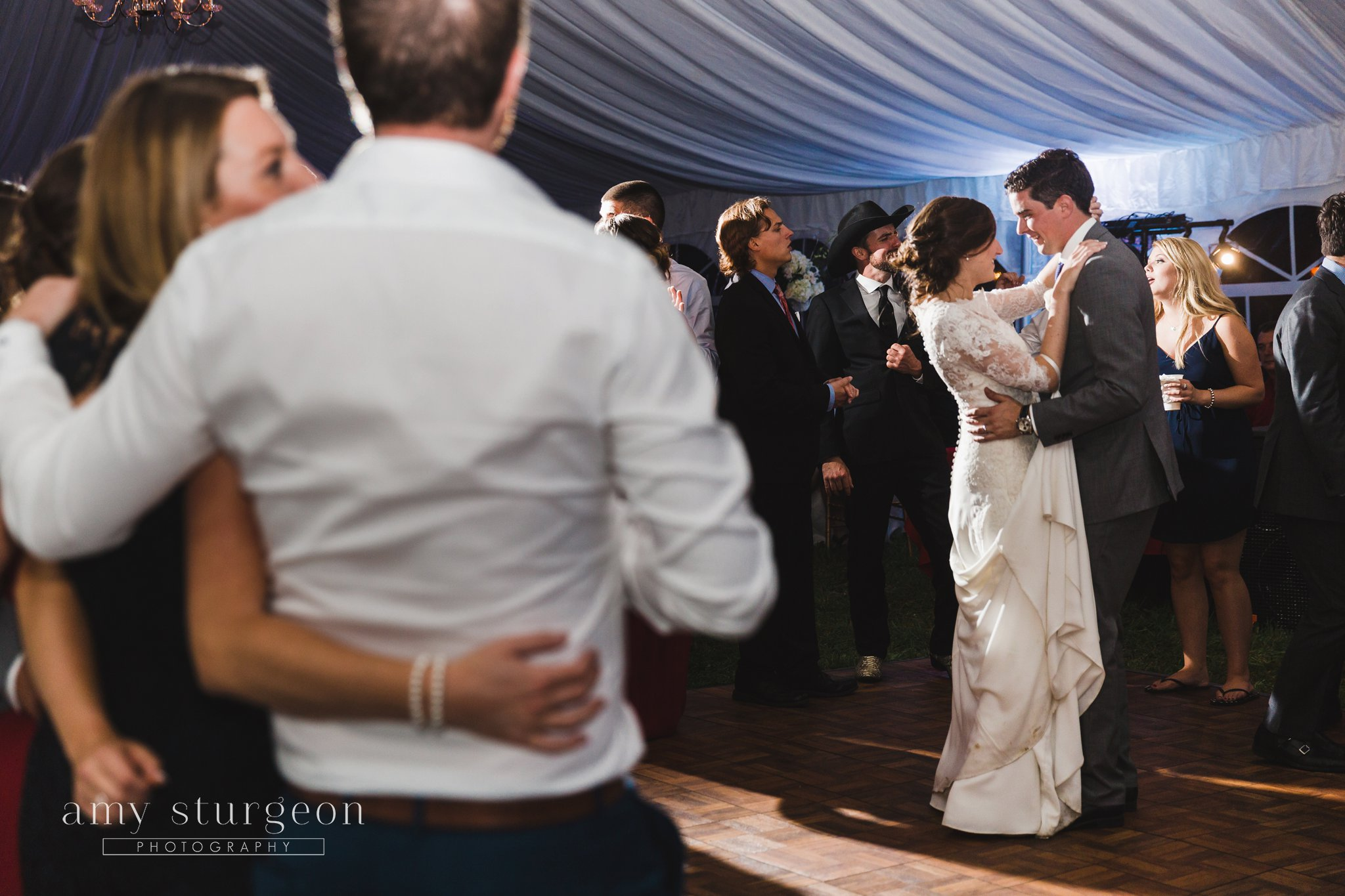 The bride and groom's first dance at an alpaca farm wedding surrounded by wedding guests