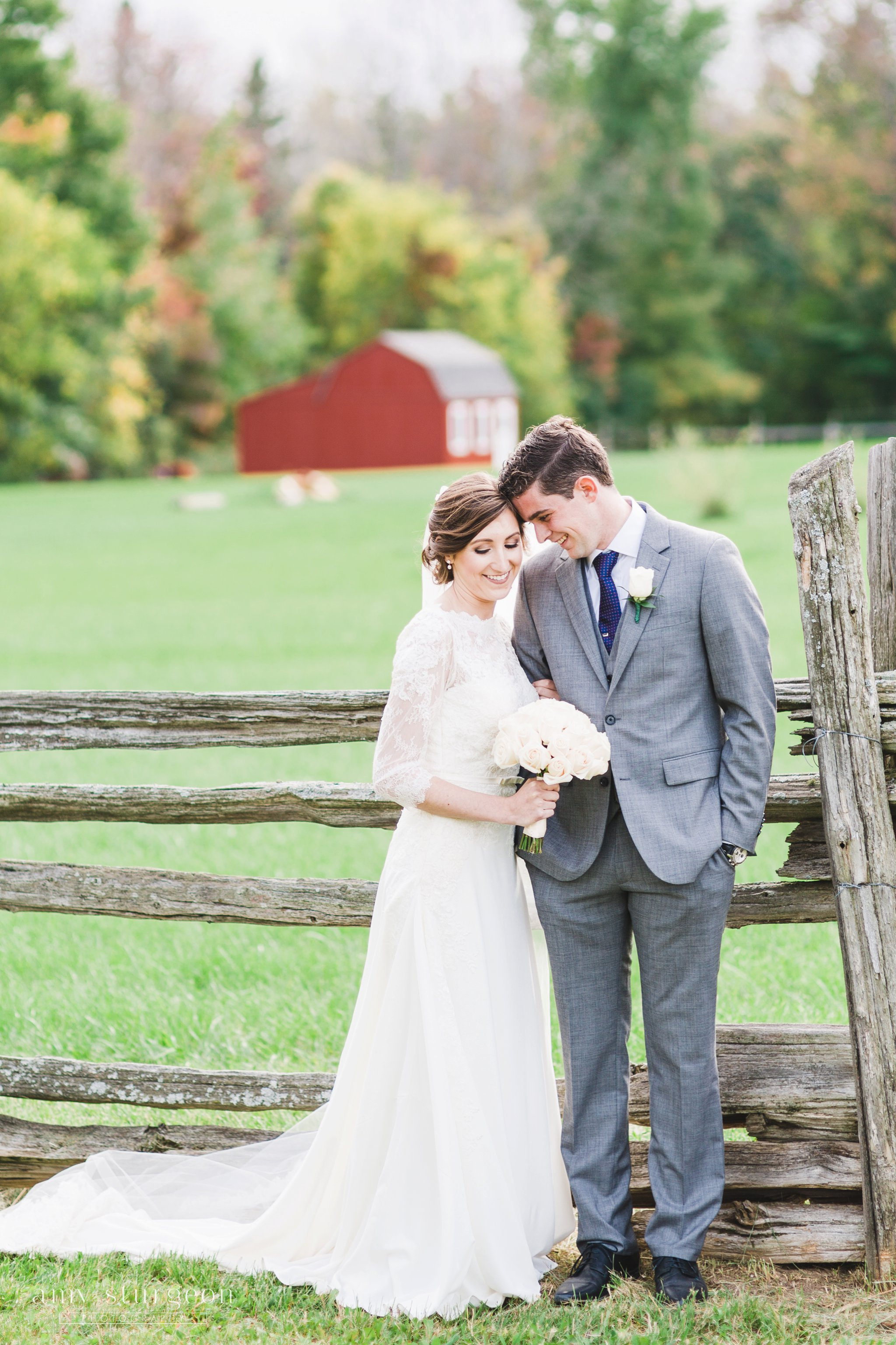 The bride and groom stood by a fence with a red barn in the background at the alpaca farm wedding