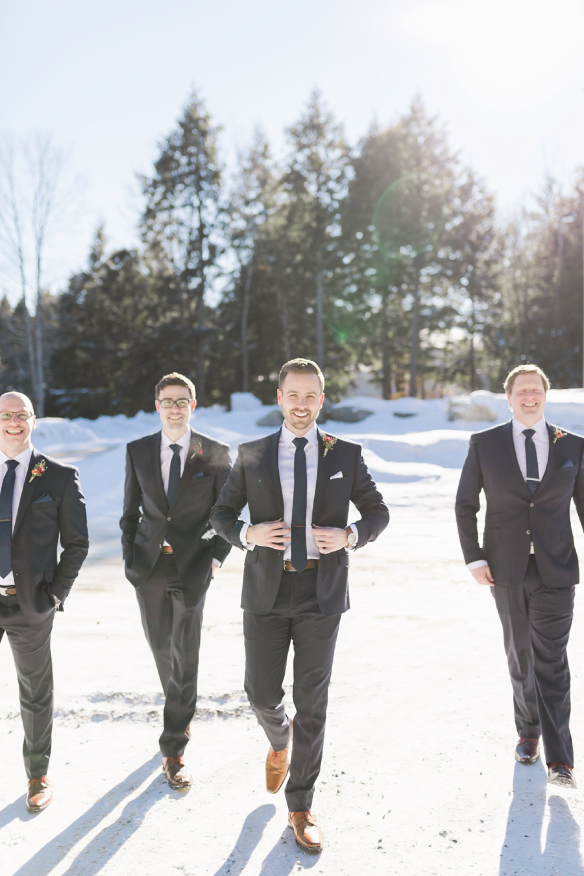 Groomsmen walk in the snow at the Winter wedding at Le Belvedere