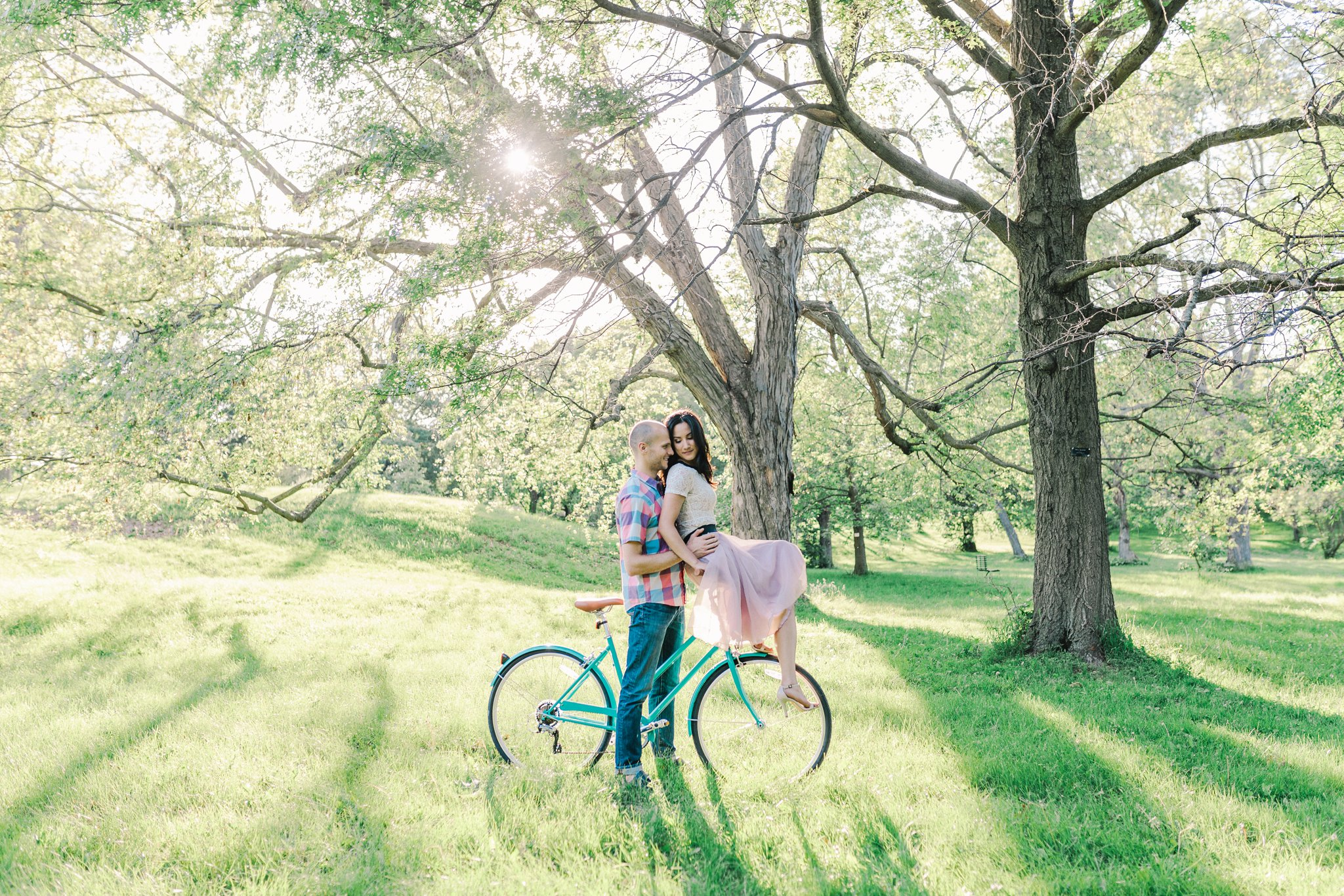 Blush tulle skirt, sitting on handlebars, teal bicycle, bicycle engagement photos in the arboretum, One Fine Beauty, Showpony Hair, Amy Pinder Photography