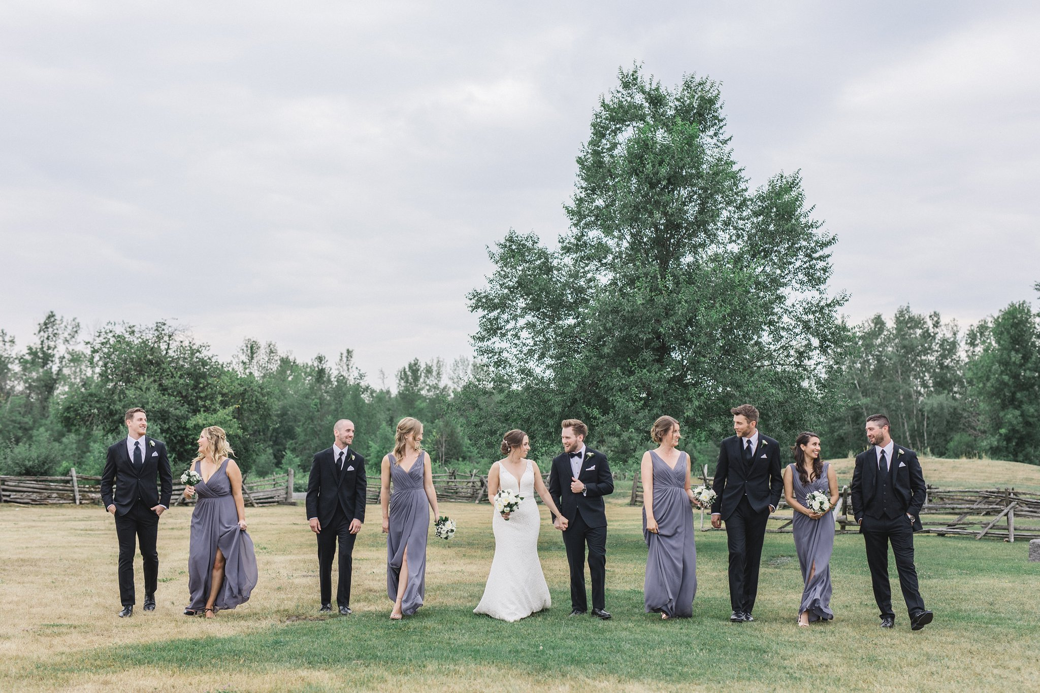 Bridal party walking in field married at Stonefields, Amy Pinder Photography