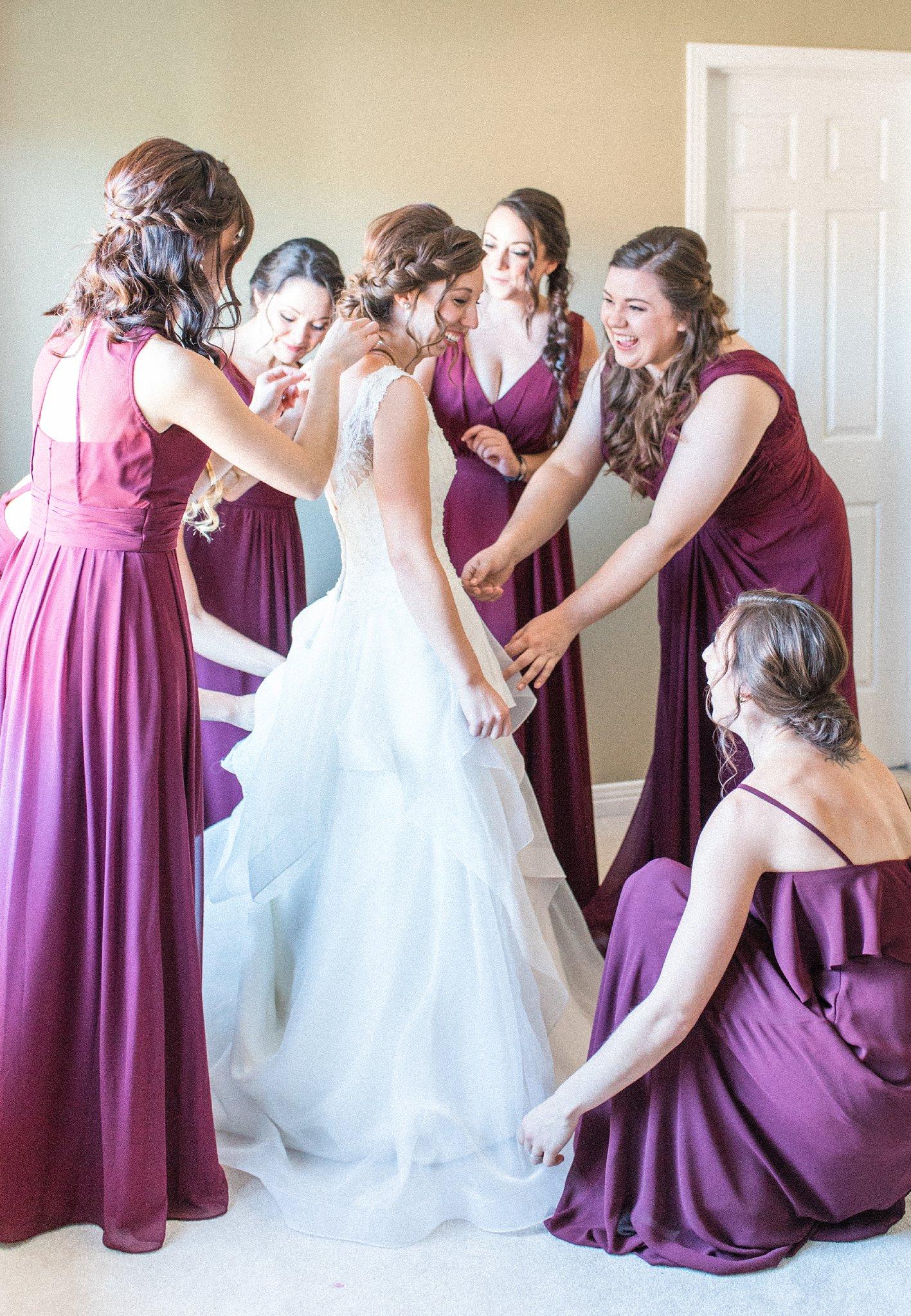 Marsala bridesmaids help bride get dressed, Hilton Garden Inn Ottawa Airport Hotel Wedding