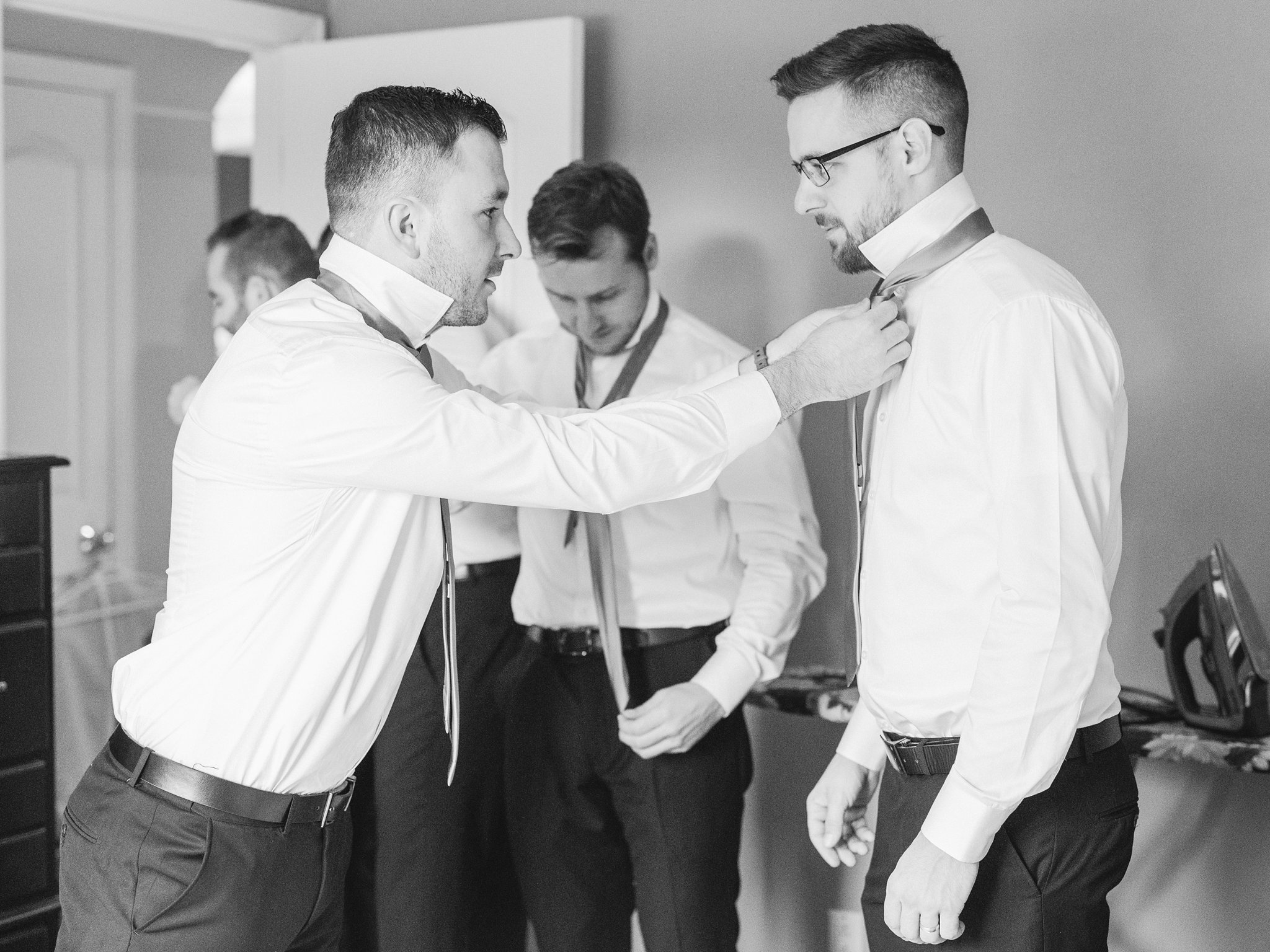 Guys tie each others ties at groom prep A Festive Fall Wedding at the Canadian Museum of Nature