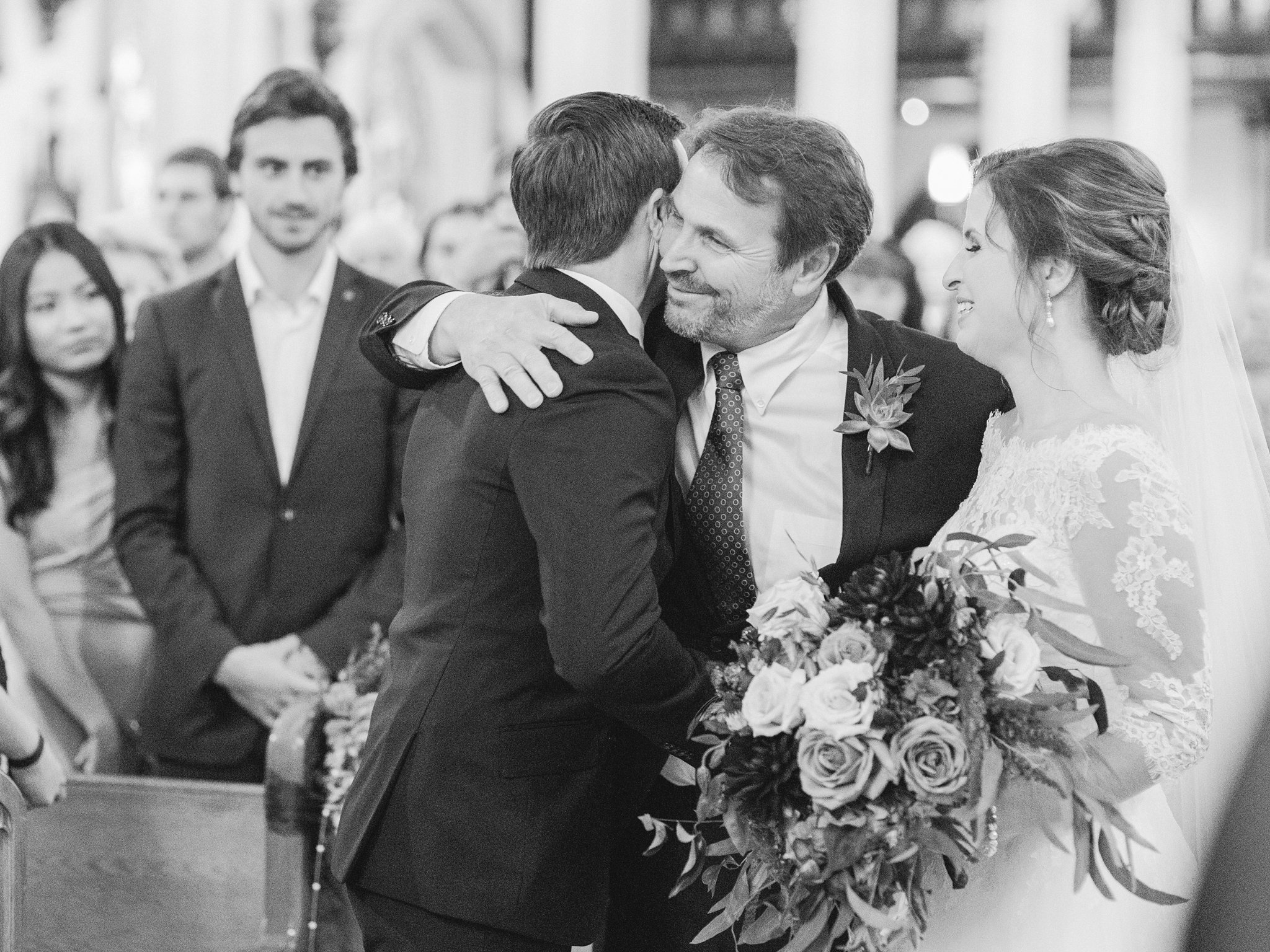 Father of the bride and groom hug at ceremony A Festive Fall Wedding at the Canadian Museum of Nature