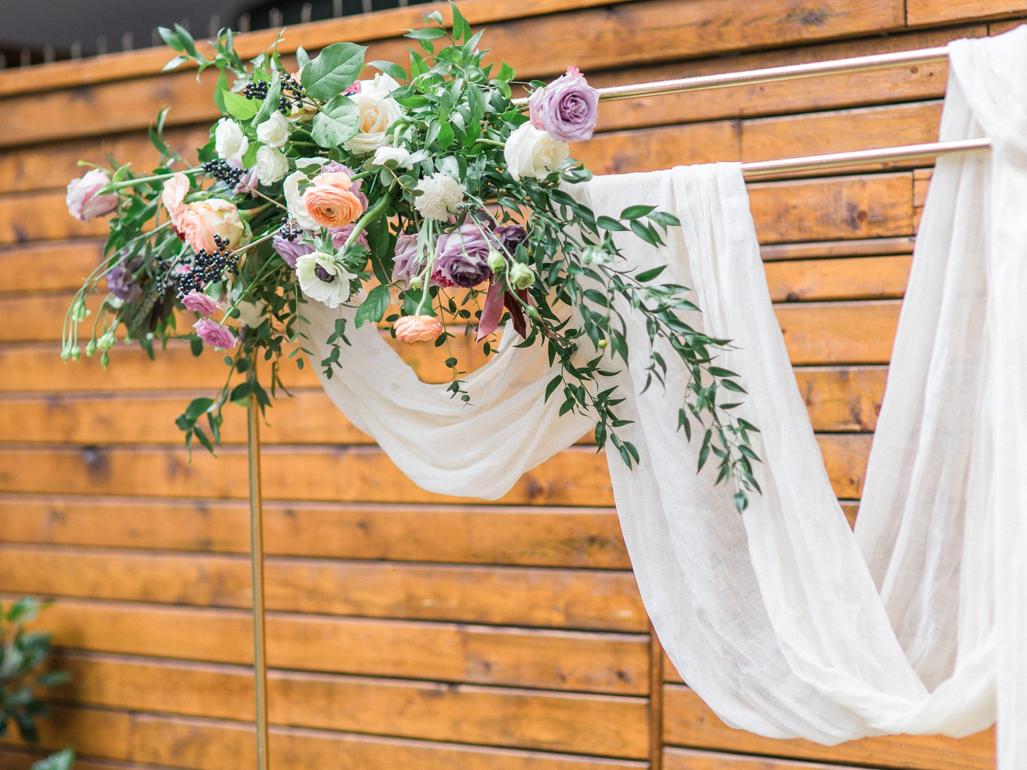 Metallic ceremony arch with florals Ottawa restaurant wedding at Sidedoor Restaurant
