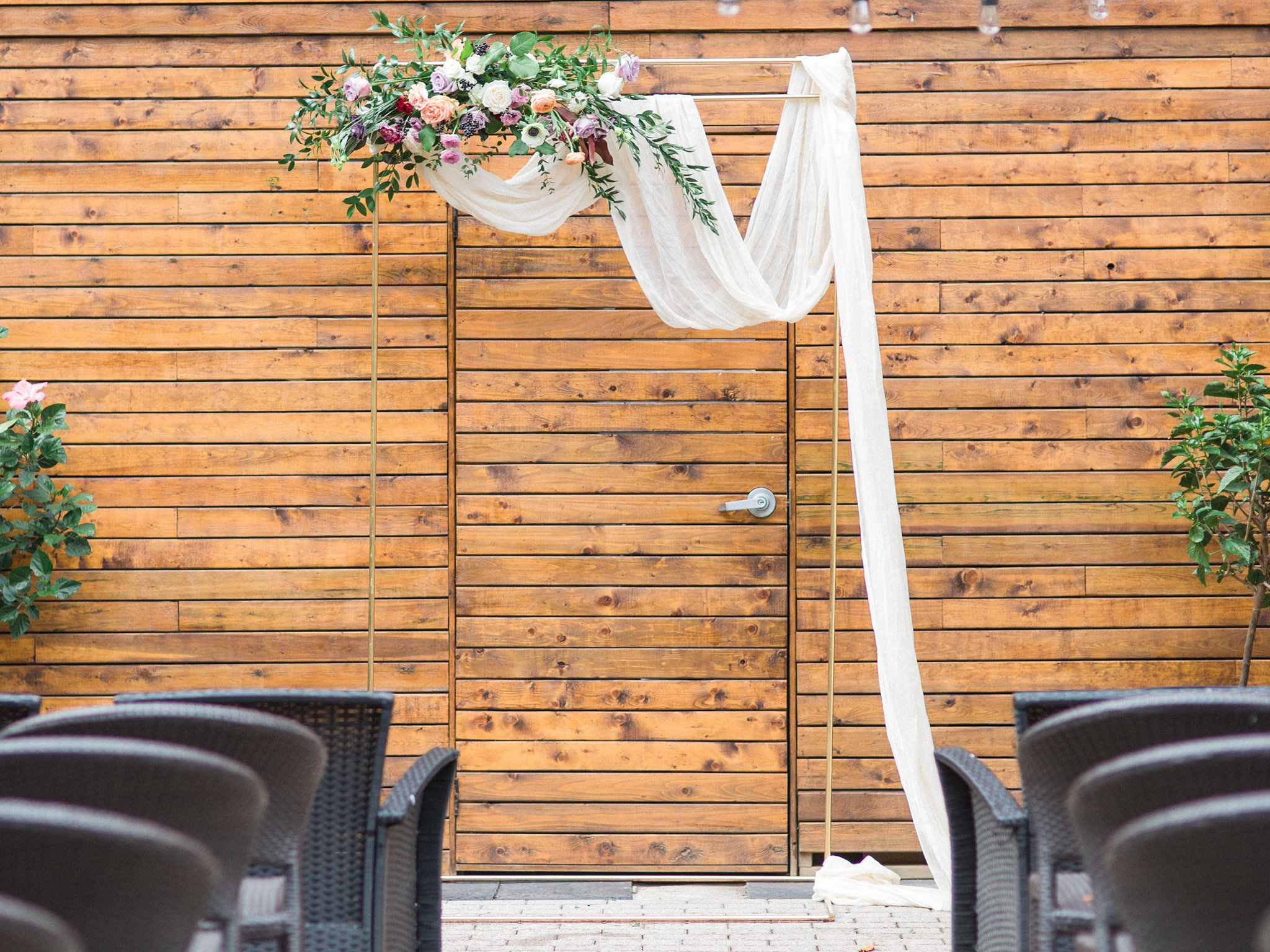 Metallic gold ceremony arch with soft drapery and florals Ottawa restaurant wedding at Sidedoor Restaurant
