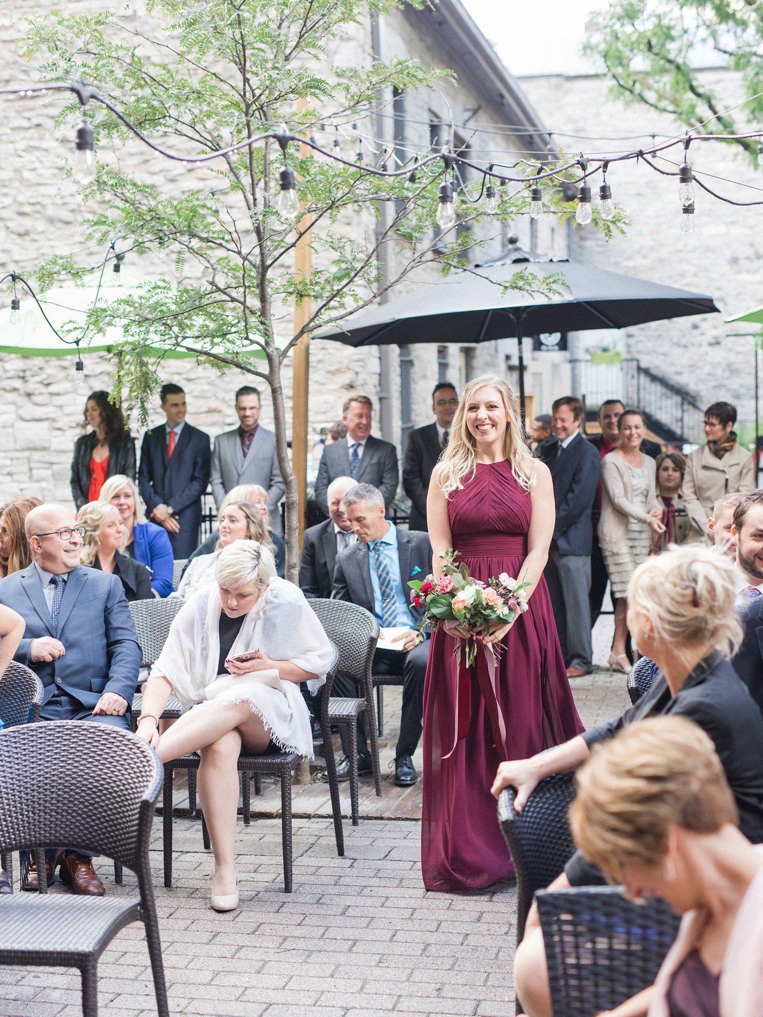 cranberry bridesmaid walking down aisle Ottawa restaurant wedding at Sidedoor Restaurant