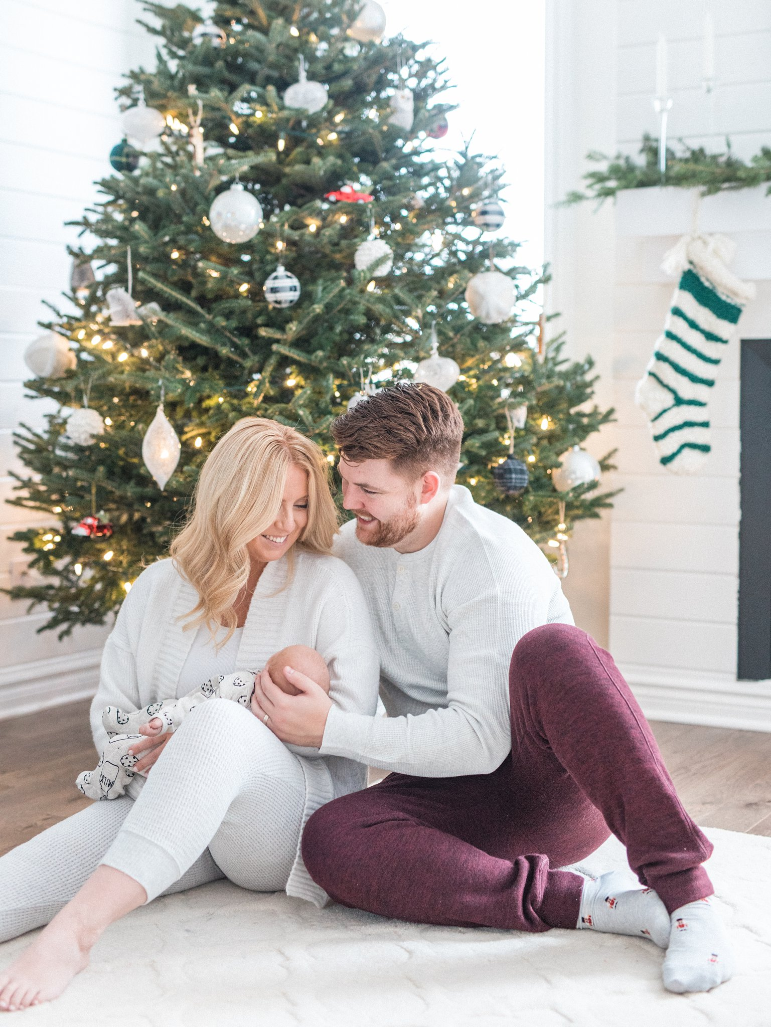 Mom and dad cuddle with baby for their Newborn Lifestyle Photos During the Christmas Holidays