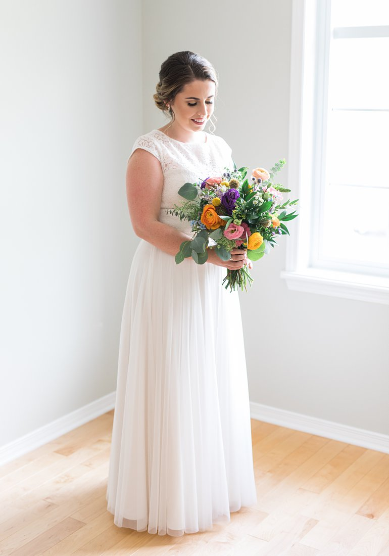 Colourful bridal bouquet, bride standing in window light, Social Restaurant Wedding Photos Ottawa
