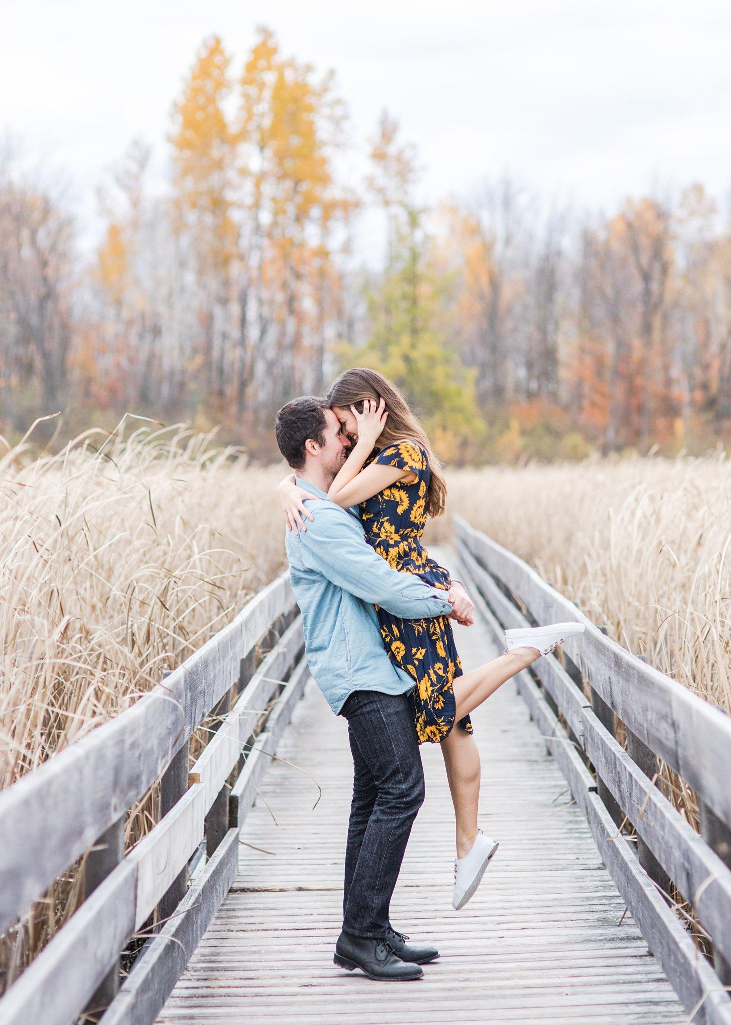 Fiance lifts his bride after proposal Mer Bleue Boardwalk Engagement Photos