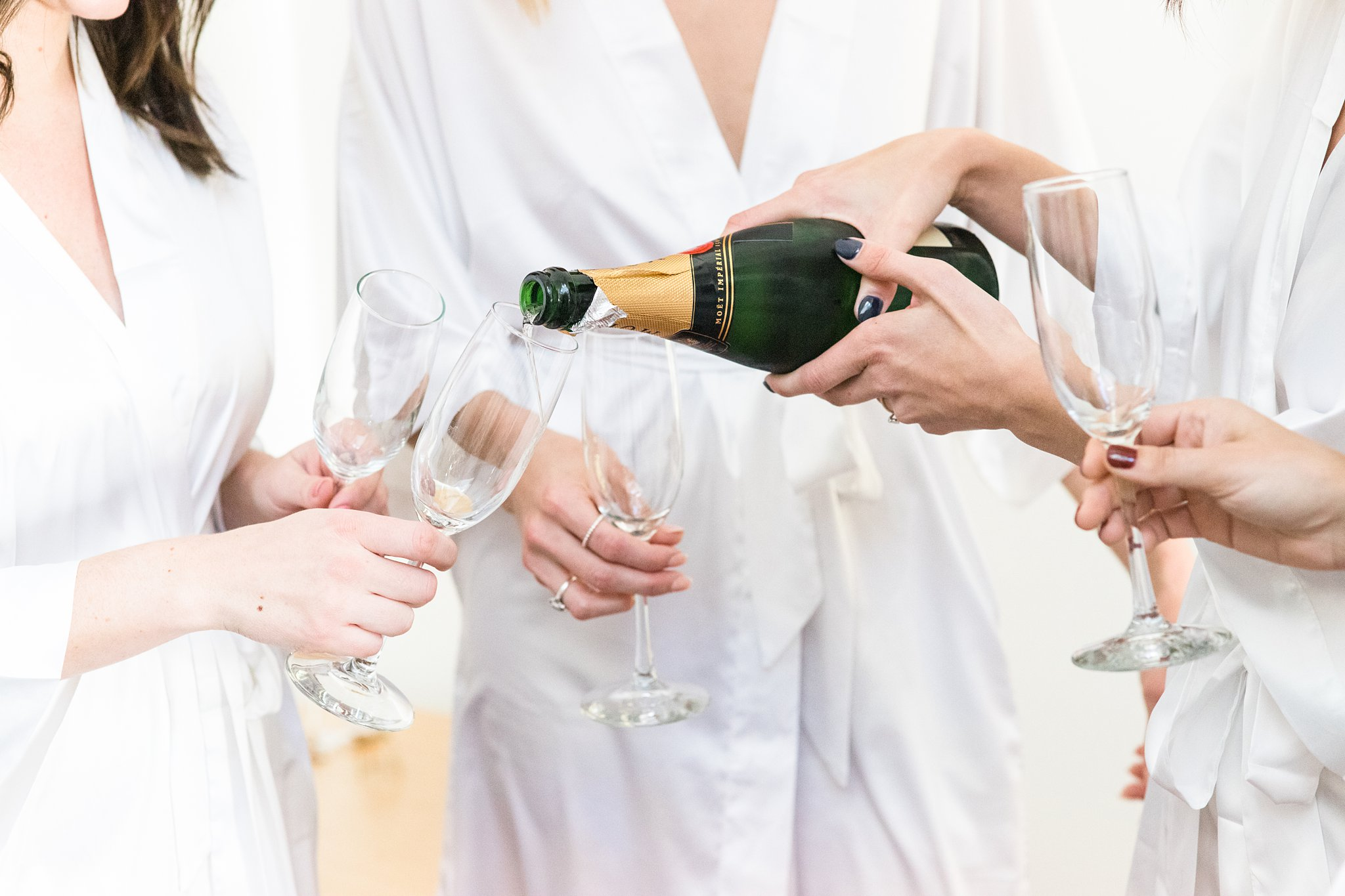 Pouring champagne in white robes on wedding day, Opinicon Wedding Photos by Amy Pinder Photography