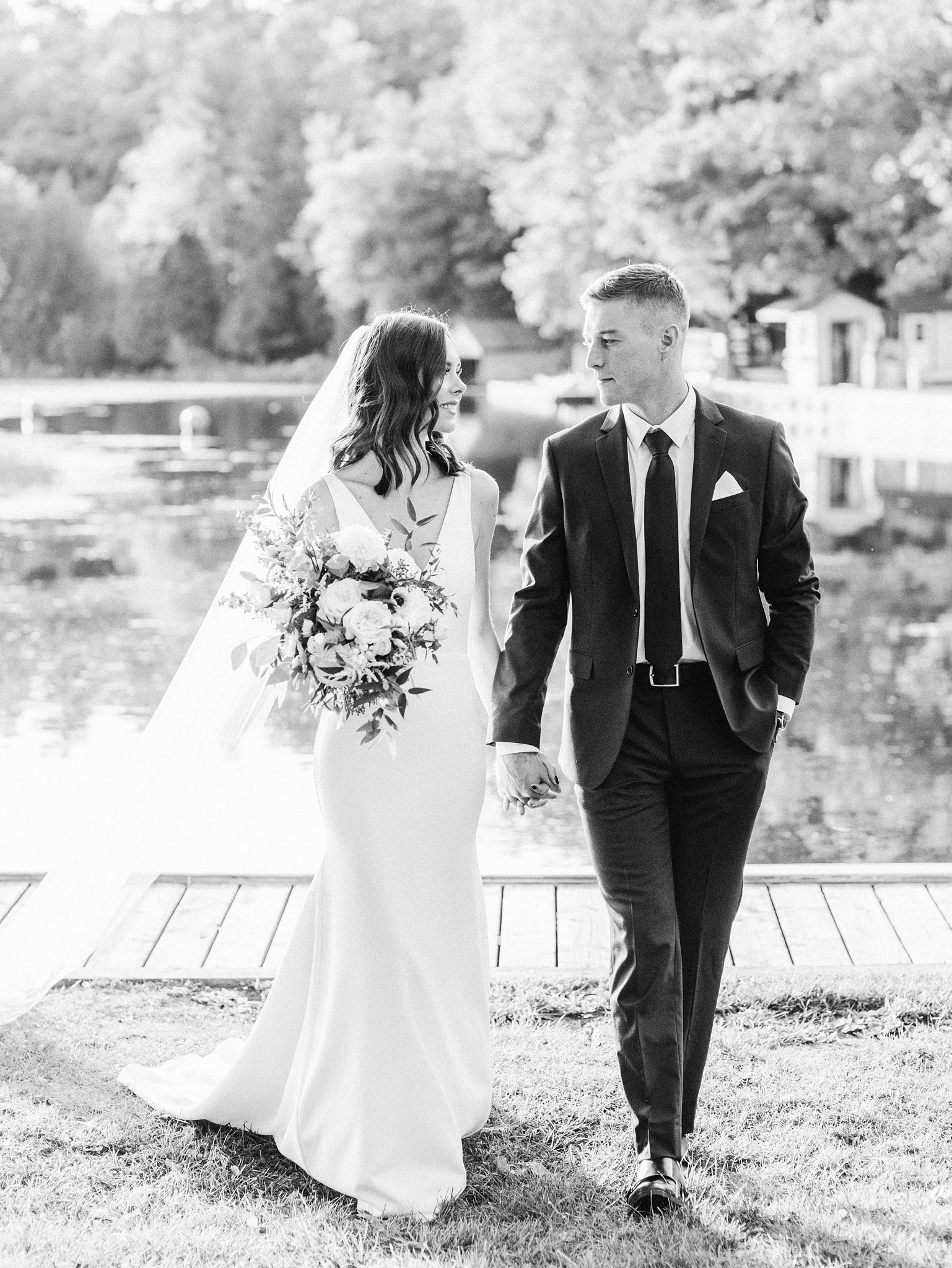 Bride and groom walk along the water, Opinicon Wedding Photos by Amy Pinder Photography