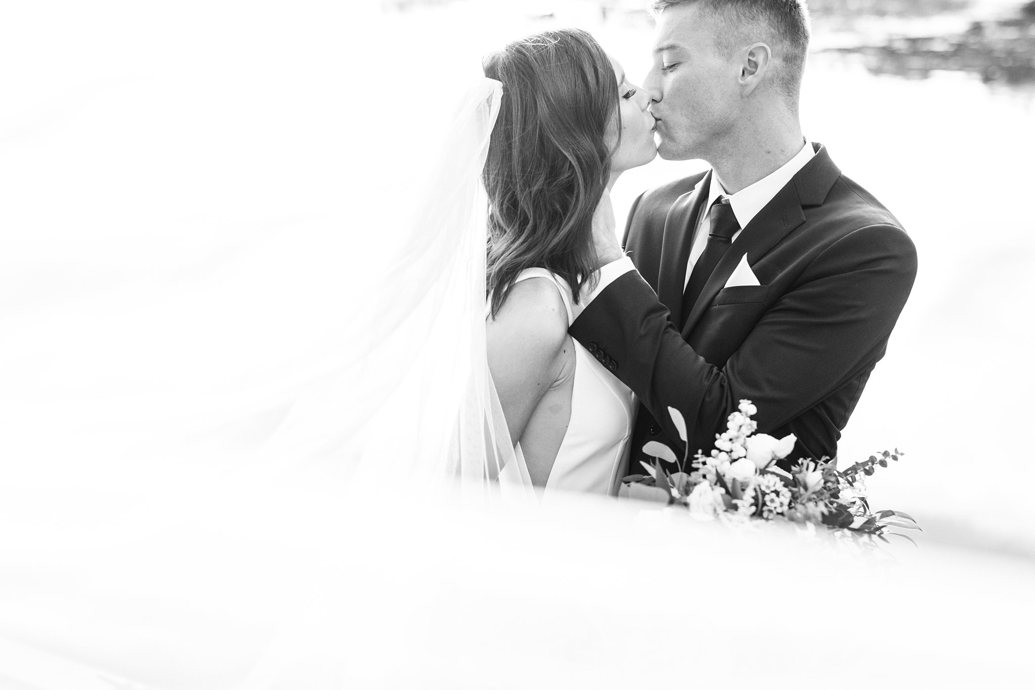 Bride and groom kiss by the water with long cathedral veil, Opinicon Wedding by Amy Pinder Photography
