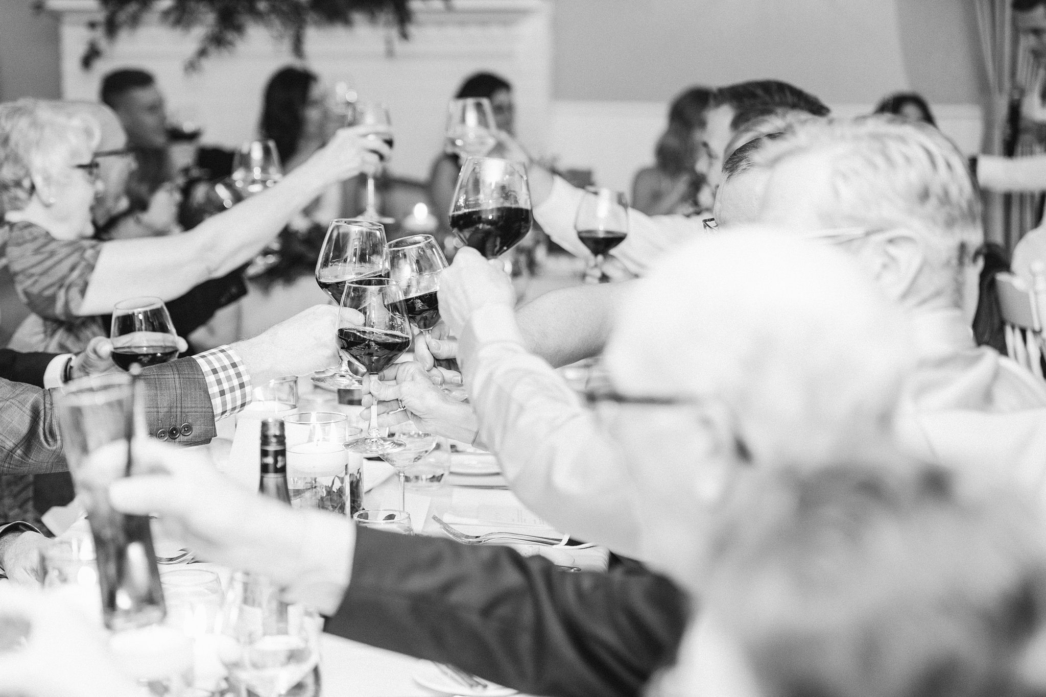 Guests cheers their wine glasses at the Opinicon Wedding by Amy Pinder Photography